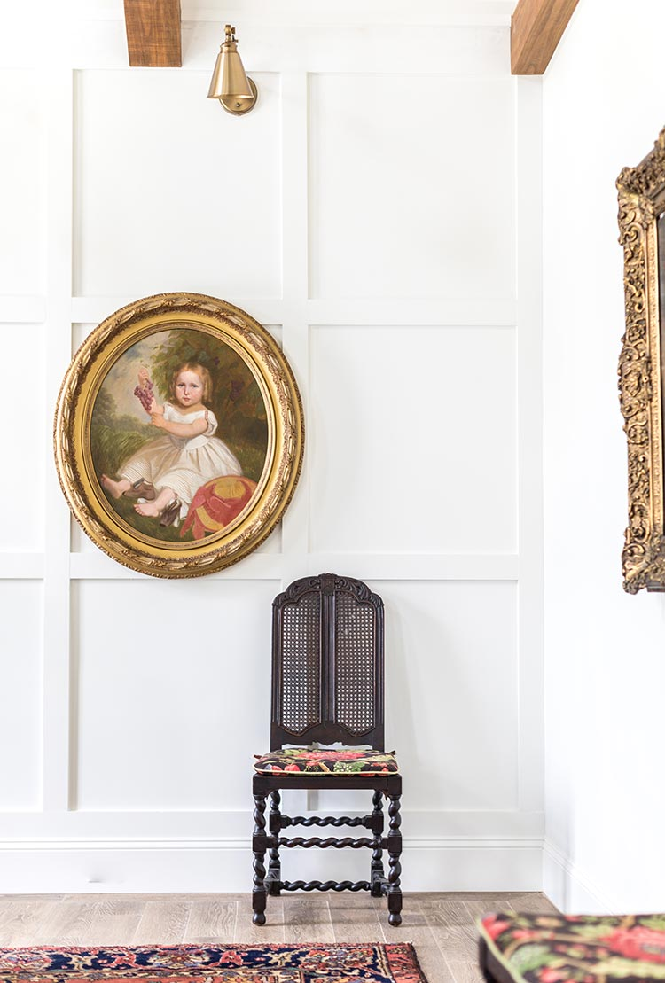 Oval classical painting of child in ornate gold frame on paneled wall.