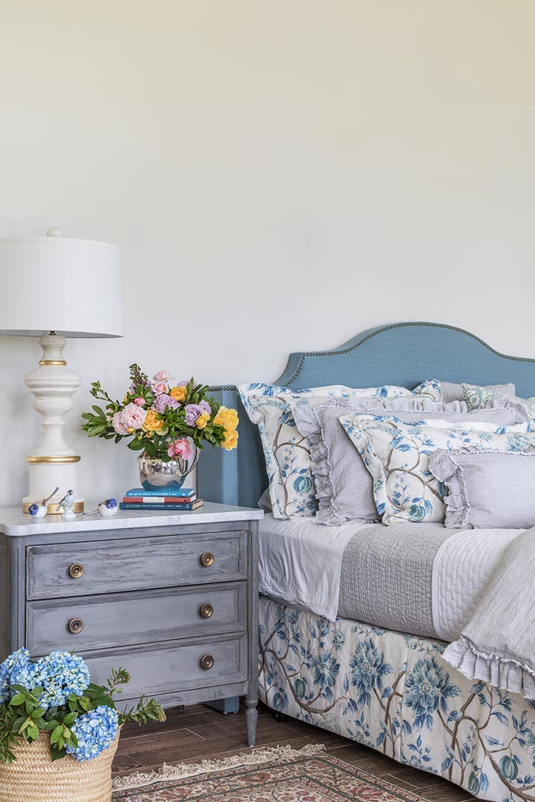 A blue bed with floral pattern linens and a gray nightstand