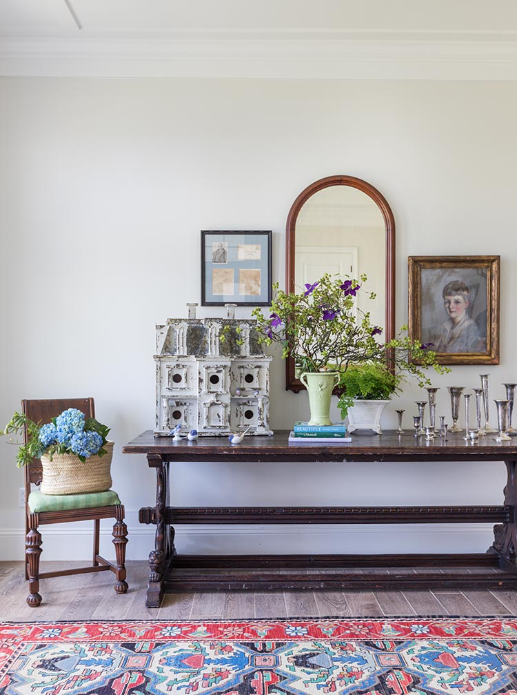 A vintage refectory table with a birdhouse and silver vases on it. A mirror and portrait hang above.
