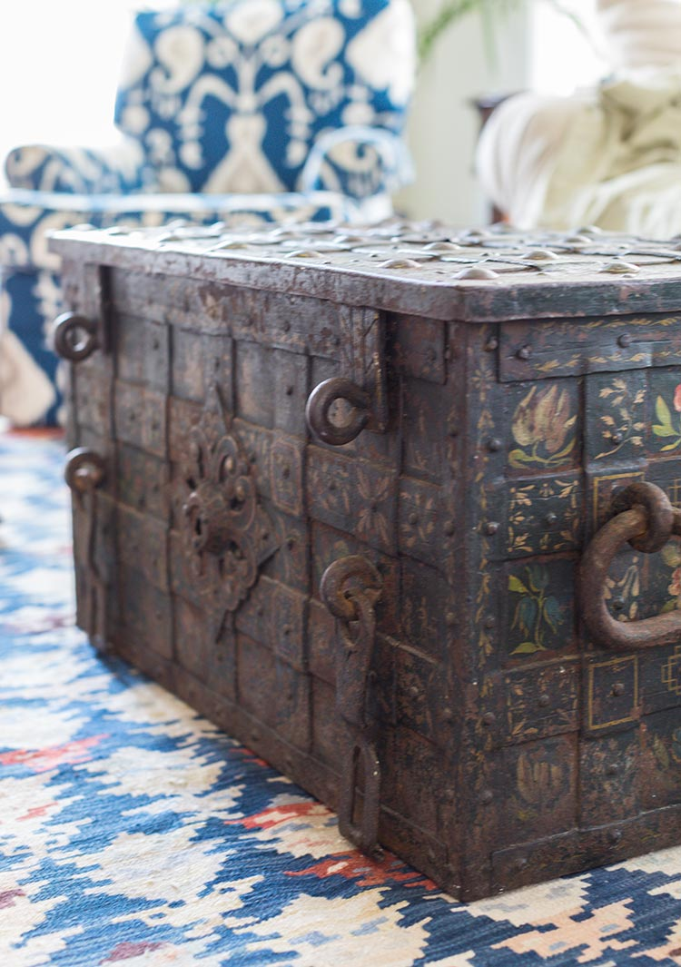 A folk-painted trunk coffee table on a blue rug