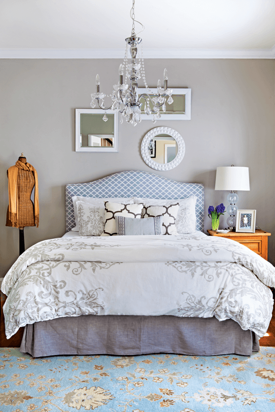 Light and bright bedroom with glossy white painted frames decorating the wall behind the headboard, with a wooden vintage dress from next to the bed.