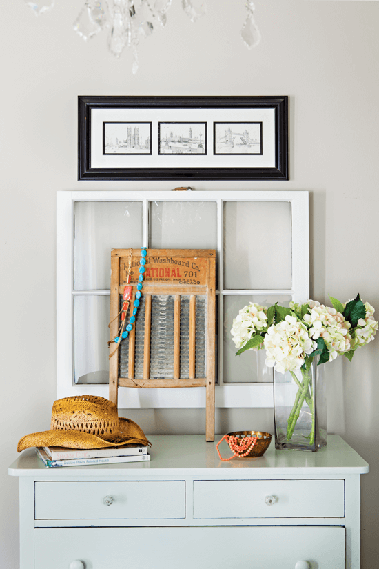 Light colored dresser against a white wall. stopped with a vase of white hydrangeas, an old window and washboard and a straw hat on top.