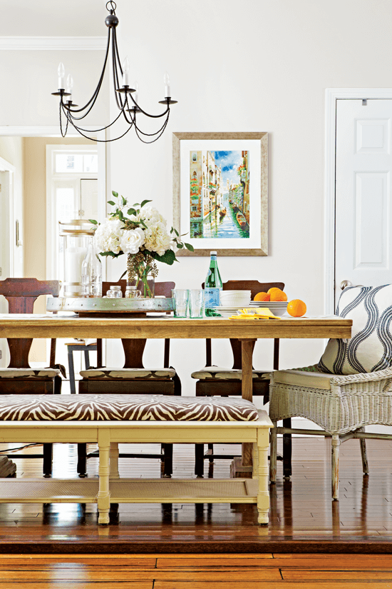 A view of the eclectic dining table set with a wicker chair, three dark wooden chairs and a light colored zebra printed upholstered bench for seating.