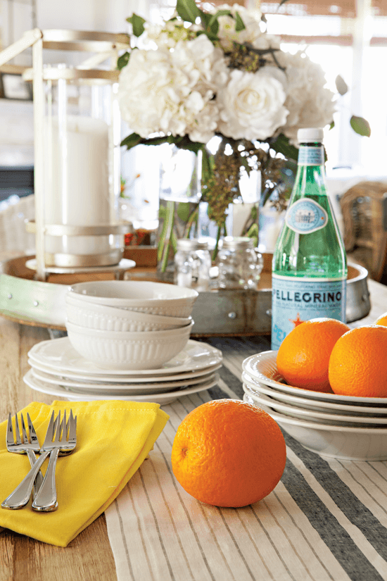 The dining table laid out with crisp and clean white dishes. Forks, bowls and sparkling water are set out with some fresh oranges on display for color and coziness.
