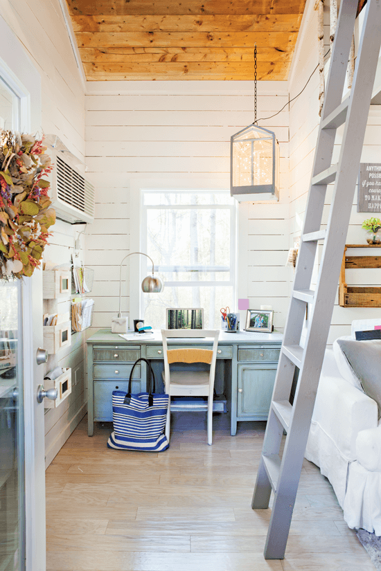 A view inside the treehouse, a tall gray ladder leads up to a hideout for the kids and straight back a small but useful desk area.