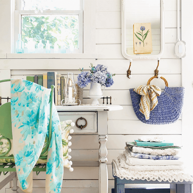 a white cottage writing desk against a shiplap wall, pretty blue linens in a stack