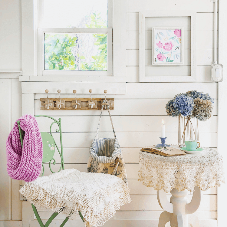 a small tea table with a lace doily, a green metal garden chair and wall hooks