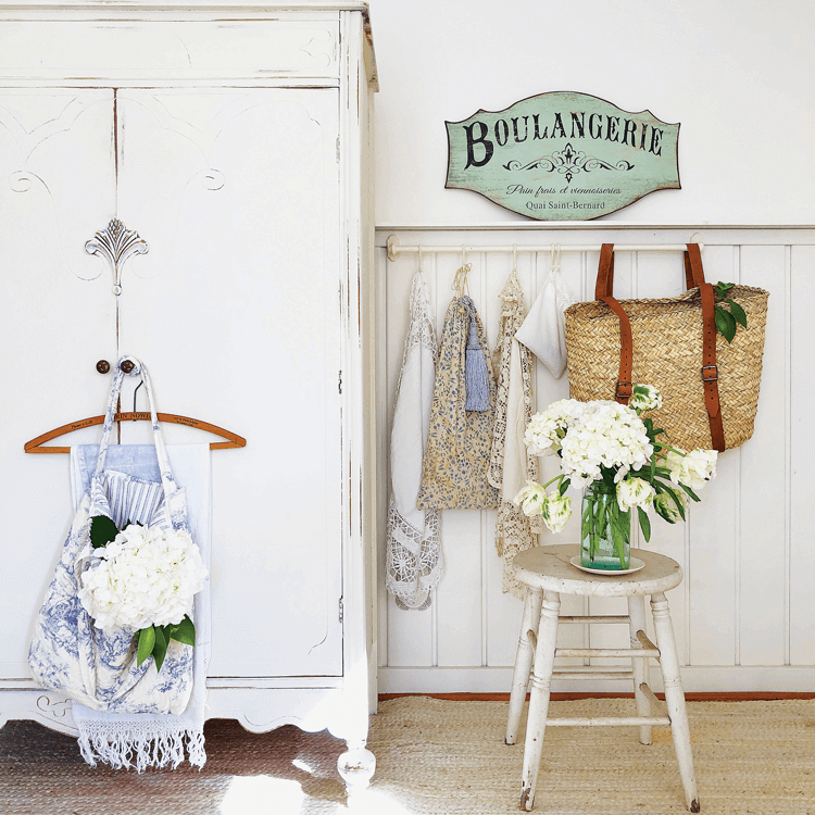 a shabby white wardrobe offeres storage in the she shed while pretty linens hang on hooks