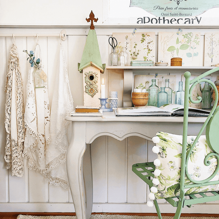 a white carved wood desk is topped with old books and garden decor