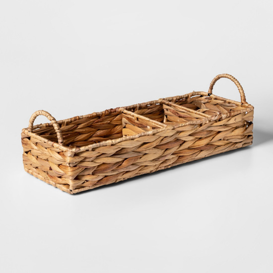 Natural thatched basket with dividers for bathroom storage.