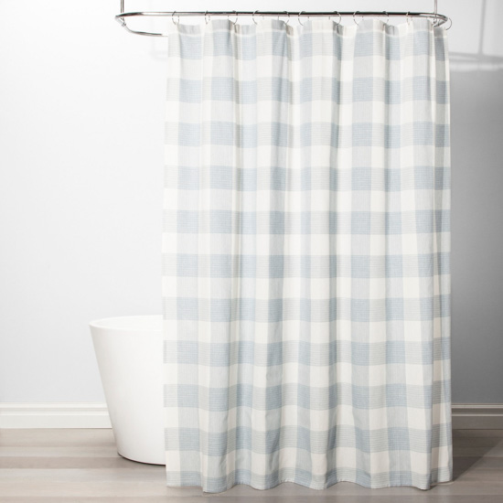 white bath tub featuring light blue and white gingham shower curtain.