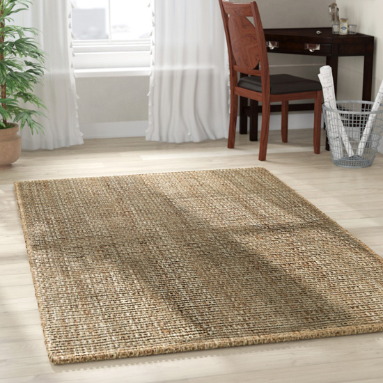 Handwoven natural colored area rug laid out on floor.