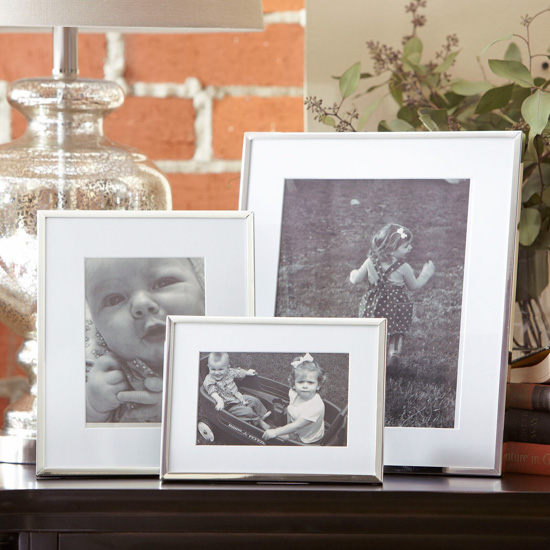 Set of 3 displayed picture frames with white matting and silver edge.
