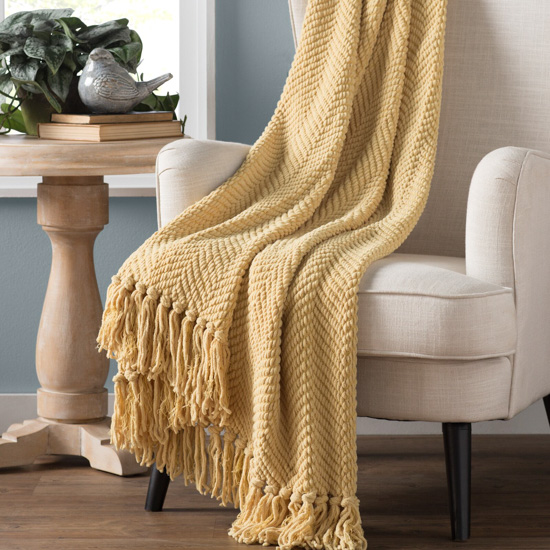 Oatmeal colored armchair with light mustard colored throw blanket draped over the top.