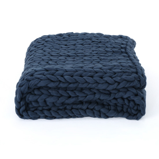 Chunky knit navy blue throw blanket, folded neatly.