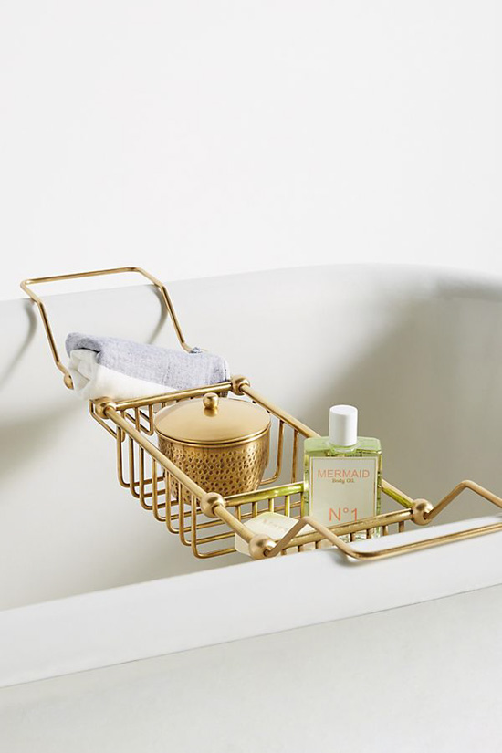 Gold, metal bath caddy perched on a bathtub and filled with shower products.