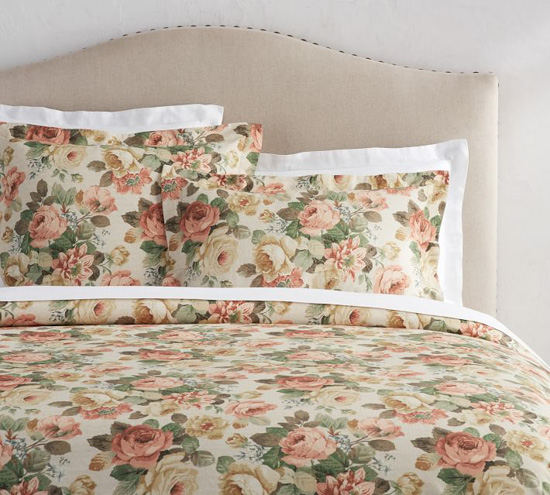 Beige upholstered headboard and floral duvet set .