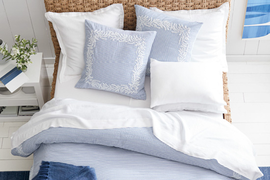 Light blue and white detailed duvet cover and pillow set displayed on a bed.