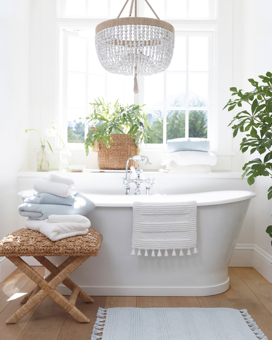 Light and airy bathroom, white free-standing tub, big window with light streaming in, house plants and featuring bath mats and towels.