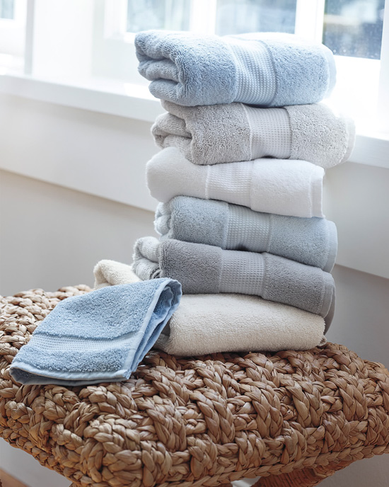 Stack of neatly folded towels in shades of blue and white.