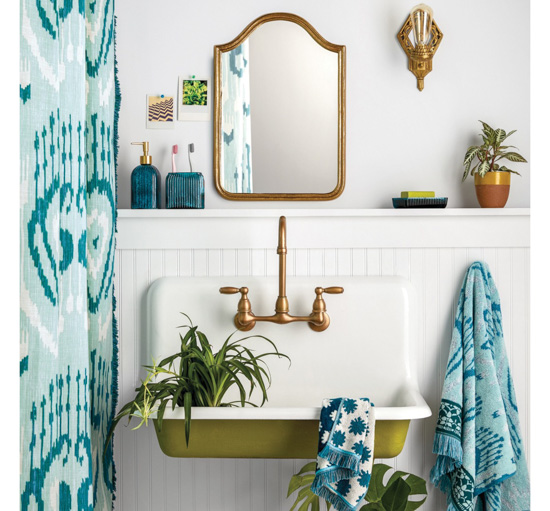 Funky cottage bathroom, all white with pops of green and blue, showing shower curtain., mirror, sink, house plants and patterned towels.