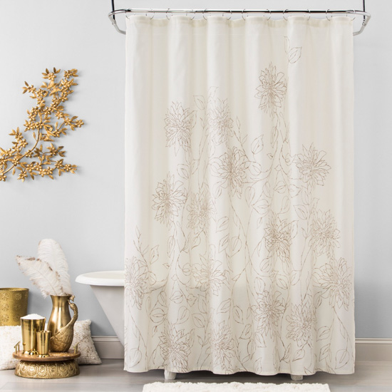 White shower curtain with gold sketched flowers on it. Bathroom scene with white tub and gold accents.