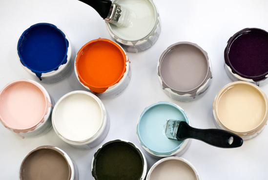 Open paint cans of various colors with one paintbrush sticking out of a can.