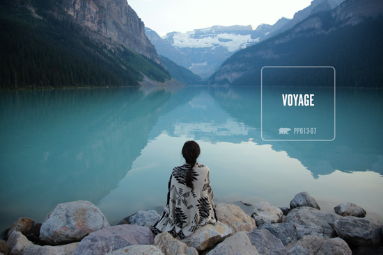 Girl sitting on rocks, wrapped in a warm blanket, looking out over mountains and a still crystal blue body of water.