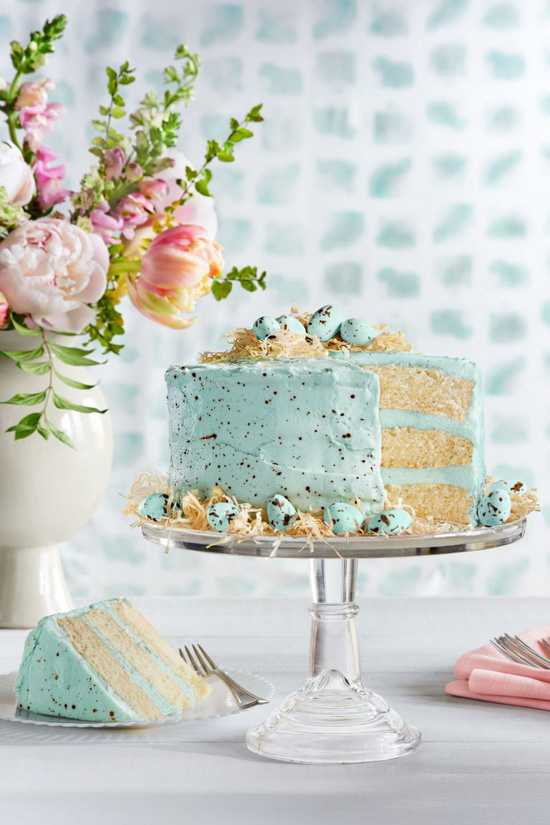 Bouquet of spring flowers, a glass cake stand topped with a three layered cake covered in a speckled robin egg blue frosting with a slice cut out and set to the side.
