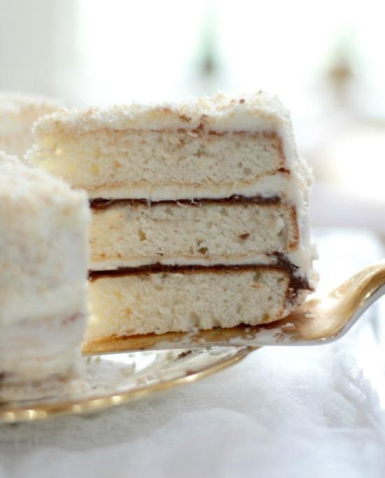 Slice of three layered white cake with Nutella layered filling being pulled out on a spatula.
