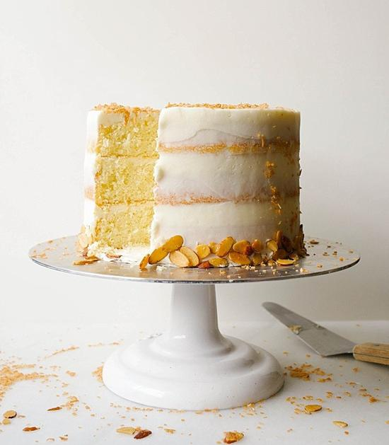 white cake stand with a three layered cake on top with a slice missing and a spatula laying on the table next to it.