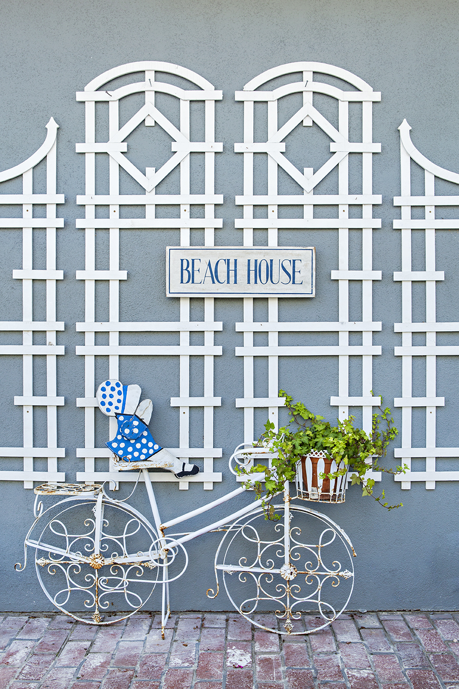 A blue exterior wall juxtaposed to a brick sidewalk with a rod iron decorative bicycle leaned against a white lattice design.