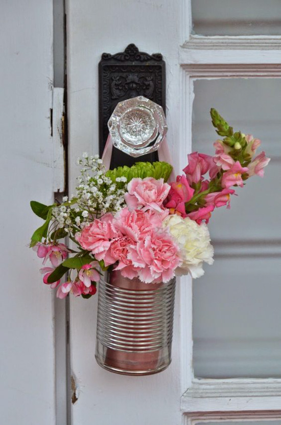 Fresh flowers in a tin can, hanging from an antique crystal doorknob.
