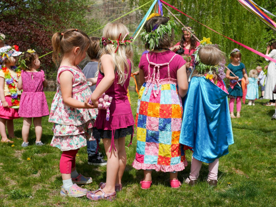 Children wearing flower crowns near the May Pole.