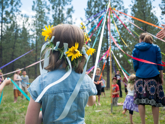 Children dancing around a May Pole holding colorful ribbons.
