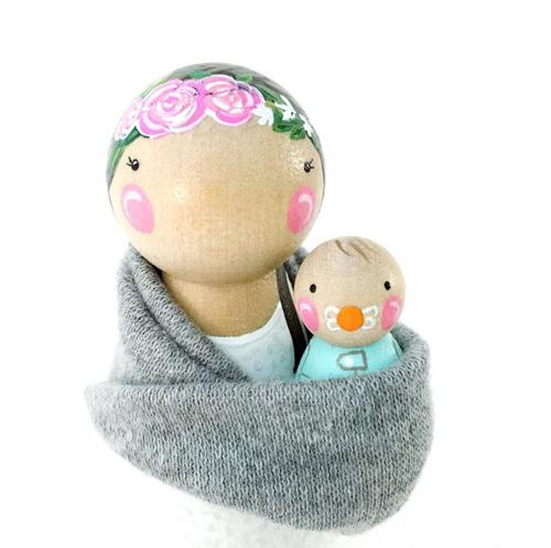 Hand painted wooden peg dolls of a mother holding a baby in a sling.