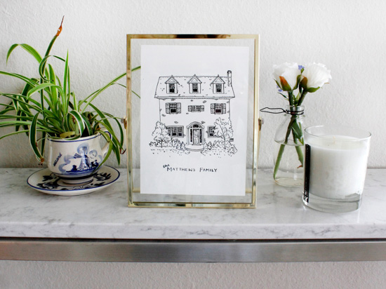 Ink on paper drawing of a custom house in a gold frame on a marble counter top.
