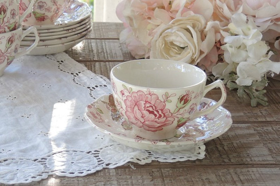 Vintage tea cup laying on a lace doily.