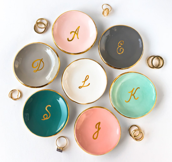 Multi-colored ring dishes with gold rims and gold monogramming in the center
