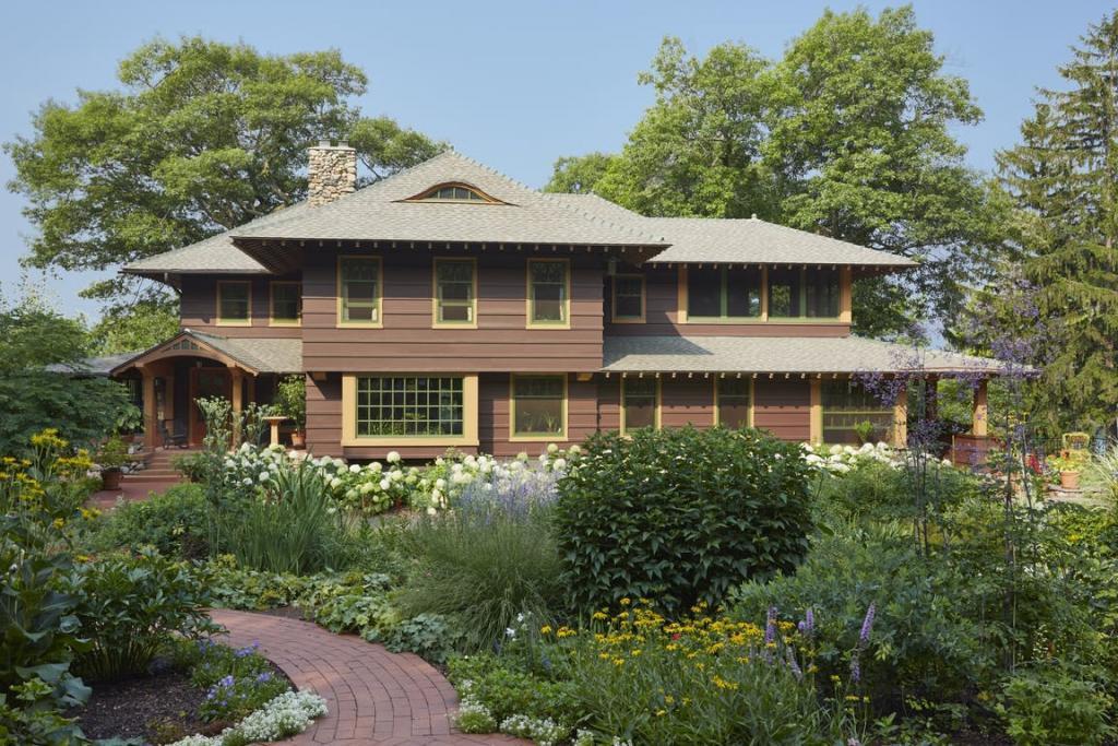 A Craftsman-style home with a natural, meadow-like garden growing in front.