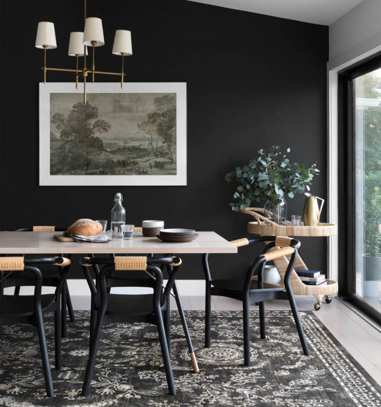 Modern dining room with large windowed wall and black back wall featuring a Rifle Paper Co. rug under the dining table.