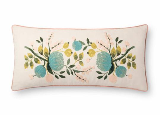 cream colored lumbar pillow with light blue and green floral design.