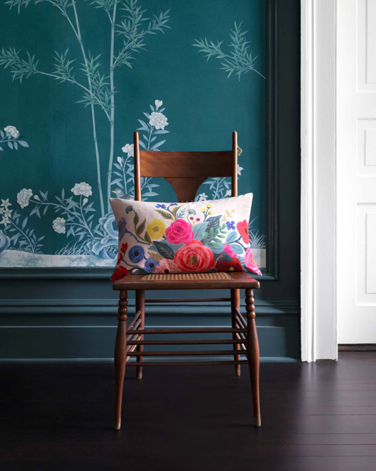 Wallapered wall with a wooden chair in front of it displaying a floral lumbar pillow.