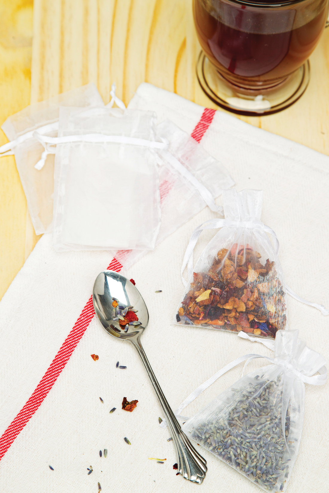 Custom filled sachets filled with loose tea blends, arranged near a clear glass mug and empty sachet bags.
