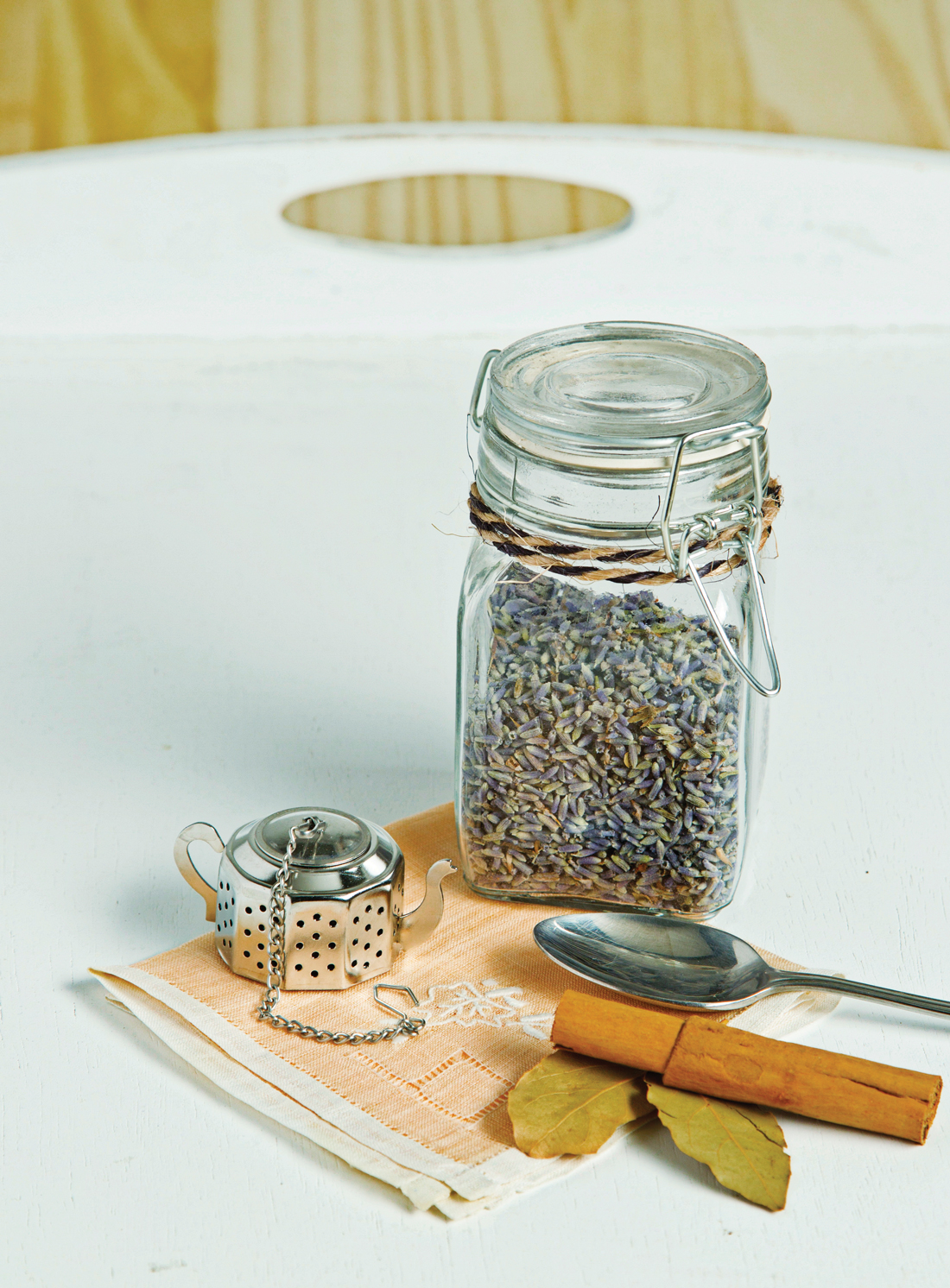 Metal teapot shaped tea diffuser, cinnamon stick, spoon, glass canister filled with lavender.