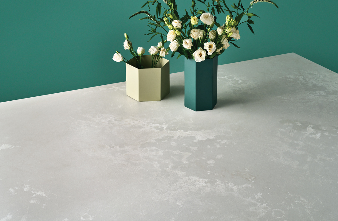 Modern looking concrete countertops with angular vases filled with fresh florals and a teal painted wall in the background.