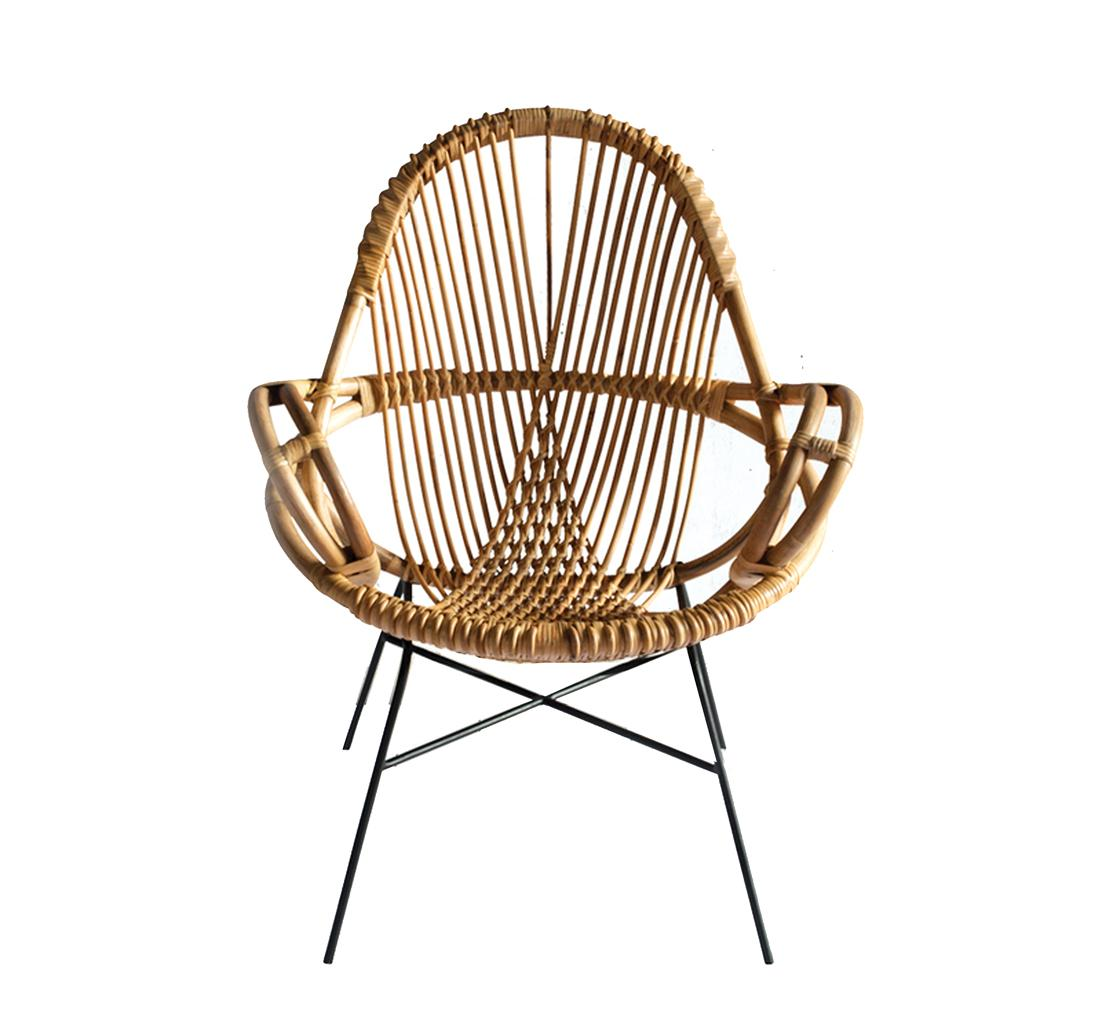 Intricate rattan chair with black metal legs.