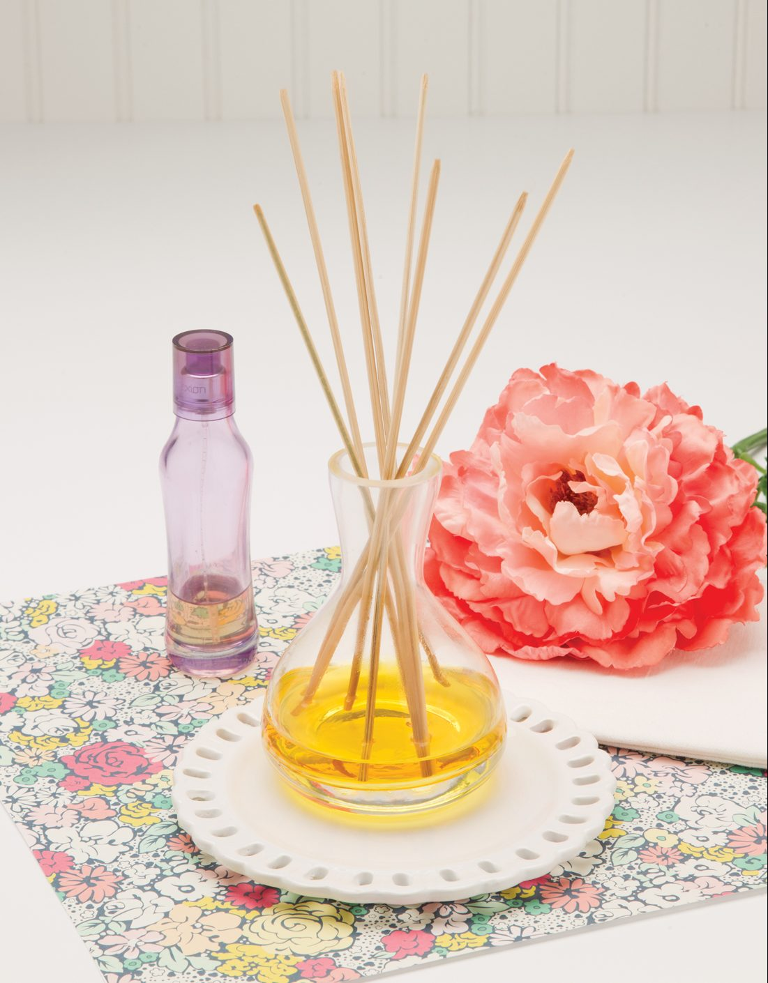 Beautifully displayed reed diffuser with light and bright colors and a coral colored rose.