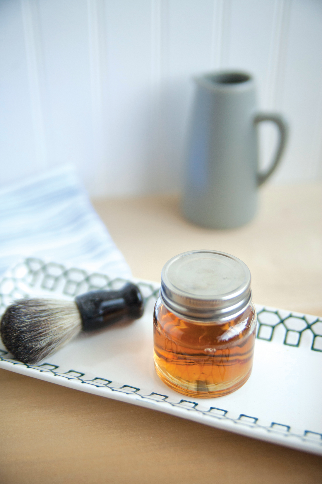 Facial brush and glass jar of golden colored beard oil.