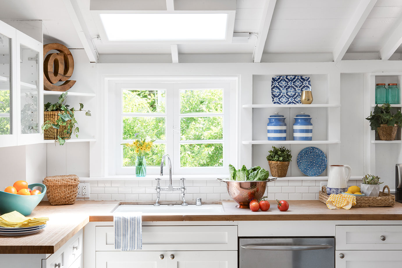 bright white kitchen with blue accents and wooden countertops.